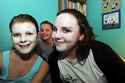 Teenage girls put on facemasks at a sleepover