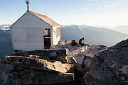 A young woman sits outside the fire lookout cabin on the summit of Hidden Lake Peaks, North Cascades National Park, Washington.