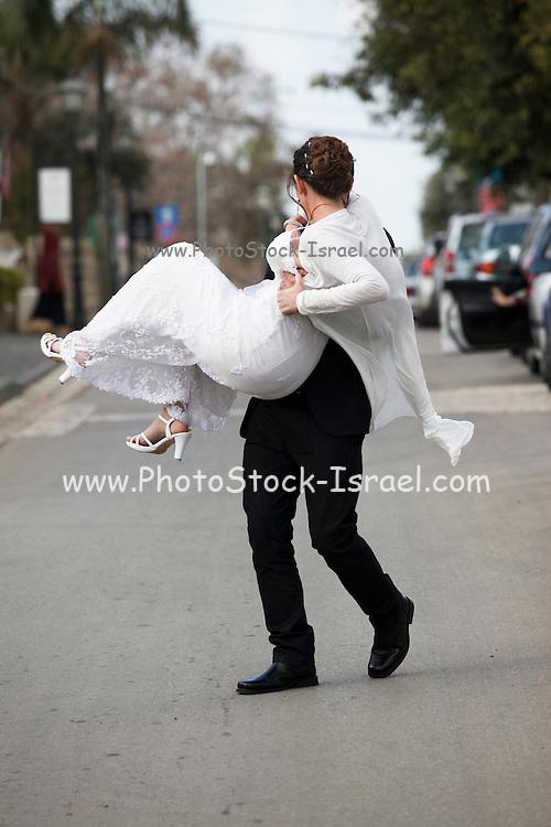 Traditional Jewish Wedding groom carries bride in street