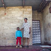 INDIVIDUAL(S) PHOTOGRAPHED: Wana Nguvu (left) and Isabel Mashau (right). LOCATION: Kuku Compound, Chitukuko, Chilanga District, Lusaka, Zambia. CAPTION: Isabel Mashau with her son Wana Nguvu at their home in Chitukuko, Lusaka. Isabel received training and helped to build a block of classrooms at the school as part of Build It International's Training into Work & Community Building programme. Build It International is a charity that trains unemployed young people in Zambia to become builders, while at the same time building vital schools and clinics in communities with little or nothing by way of resources.