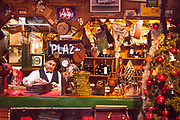 Mozo ( waiter) behind bar at Volver, famous old seafood cafe on waterfront Beagle Channel, Ushuaia, Argentina