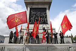 © Licensed to London News Pictures.01/05/2017. London, UK. Communist Party flags are flown by activists attending the May Day march in Trafalgar Square on May 1, 2017. Photo credit: Tom Nicholson/LNP