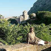 MOSTAR, BOSNIA AND HERZEGOVINA - JUNE 28:  A Muslim girl poses in front of the Old Bridge on June 28, 2013 in Mostar, Bosnia and Herzegovina. The Siege of Mostar reached its peak and more cruent time during 1993. Initially, it involved the Croatian Defence Council (HVO) and the 4th Corps of the ARBiH fighting against the Yugoslav People's Army (JNA) later Croats and Muslim Bosnian began to fight amongst each other, it ended with Bosnia and Herzegovina declaring independence from Yugoslavia.  (Photo by Marco Secchi/Getty Images)