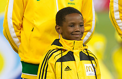 Boy standing in front a Brazil football player during the 2010 FIFA World Cup South Africa Group G Second Round match between Brazil and République de Côte d'Ivoire on June 20, 2010 at Soccer City Stadium in Soweto, suburban Johannesburg, South Africa.  Brazil defeated Ivory Coast 3-1. (Photo by Vid Ponikvar / Sportida)
