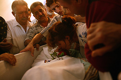 Family members mourn the loss of loved ones  in Baghdad, Iraq on Aug. 20, 2003. The previous day, a family member who was a taxi driver, was waiting for UN officials outside the building when a cement truck packed with explosives detonated outside the offices of the UN headquarters in Baghdad, Iraq, killing 20 people and devastating the facility in an unprecedented suicide attack against the world body. At least 100 people were wounded.