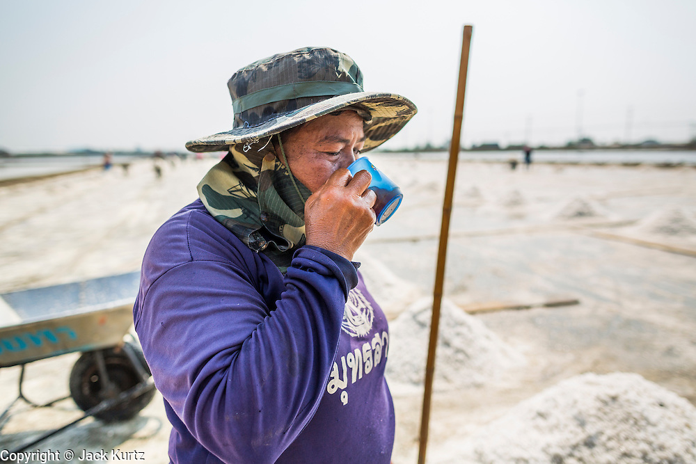 """28 MARCH 2014 - NA KHOK, SAMUT SAKHON, THAILAND: A Thai salt worker drinks an iced tea from a shared cup in a salt evaporation pond in Samut Sakhon province. Thai salt farmers south of Bangkok are experiencing a better than usual year this year because of the drought gripping Thailand. Some salt farmers say they could get an extra month of salt collection out of their fields because it has rained so little through the current dry season. Salt is normally collected from late February through May. Fields are flooded with sea water and salt is collected as the water evaporates. Last year, the salt season was shortened by more than a month because of unseasonable rains. The Thai government has warned farmers and consumers that 2014 may be a record dry year because an expected """"El Nino"""" weather pattern will block rain in mainland Southeast Asia. Salt has traditionally been harvested in tidal basins along the coast southwest of Bangkok but industrial development in the area has reduced the amount of land available for commercial salt production and now salt is mainly harvested in a small parts of Samut Songkhram and Samut Sakhon provinces.    PHOTO BY JACK KURTZ"""
