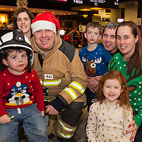 Gene, Chris, Evan, Noel, Mary and Anna Gore from Meelick with Shannon Airport Firefighter Ger O'Shea at Santa's Flights at Shannon Airport