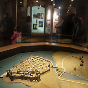 A model depicting how Caernarfon Castle would have looked in its heyday as part of an exhibit on the castle, with tourists in the background.