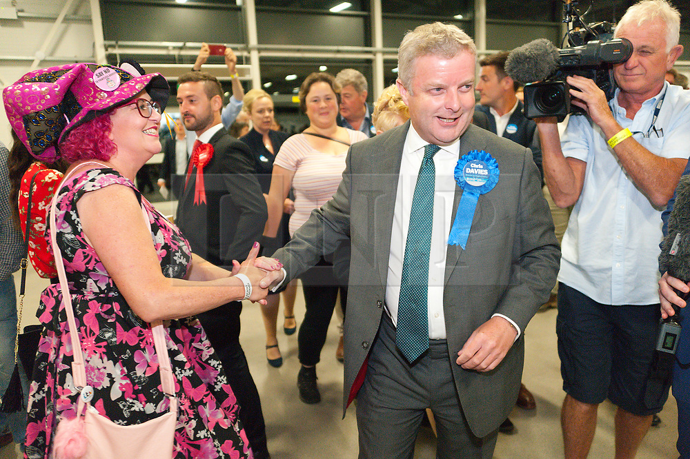 © Licensed to London News Pictures. 01/08/2019. Llanelwedd, Powys, UK. Chris Davies (Conservative candidate) greet Lady Lily the Pink. Jane Dodds Liberal Democrats wins the by-election. The Brecon & Radnorshire by-election count takes place in the Food Hall of the Royal Welsh Agricultural Society showground. <br /> The by-election has been recalled because the incumbent Tory MP. Chris Davies, who has been convicted for faking expenses claims, has been booted from the seat after a recall petition was passed when more than 10,000 voters backed the move. <br /> Candidates for the by-election are: Brexit Party - Des Parkinson. Conservative - Christopher Davies. Labour - Tom Davies. Liberal Democrats - Jane Dodds. Monster Raving Loony - Lady Lily the Pink. UKIP - Liz Phillips. Photo credit: Graham M. Lawrence/LNP