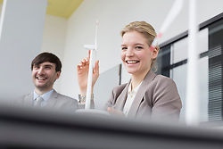 Businesswoman and man with wind power model, smiling