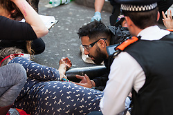 London, UK. 20th April 2019. Police officers remove Hanna, a seven-months pregnant climate change campaigner from Extinction Rebellion, who had locked herself to a fellow activist using an arm tube at Oxford Circus following a policing operation to clear it of protesters earlier in the day. The heart of London's shopping district was blocked until late afternoon by lock-ons on the sixth day of International Rebellion activities to call on the British government to take urgent action to combat climate change.