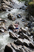 Feshiebridge is a popular stop and place to swim in the ice cold River Feshie in summer time. Here a man works his way up the river jumping from rock to rock in the wild waters. The river comes from the Cairngorm mountains and runs into the River Spey.
