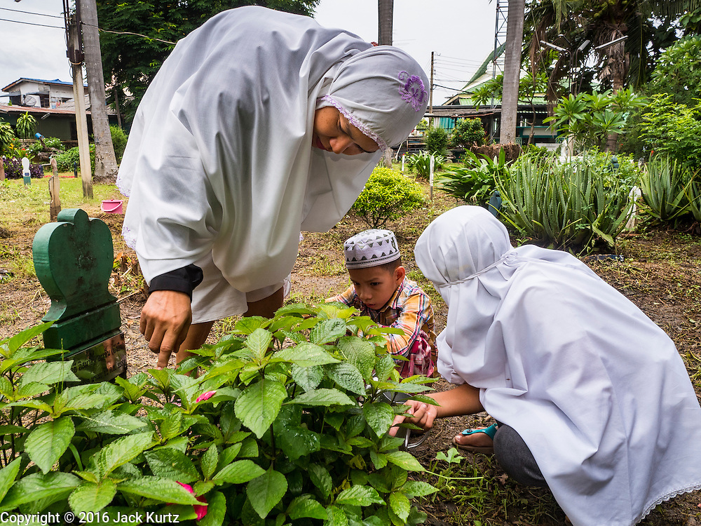 06 JULY 2016 - BANGKOK, THAILAND:  A family cleans up a relative's grave in the cemetery at Bang Luang Mosque in the Thonburi section of Bangkok. It is traditional for people to clean the graves of family members after Eid. Eid al-Fitr is also called Feast of Breaking the Fast, the Sugar Feast, Bayram (Bajram), the Sweet Festival or Hari Raya Puasa and the Lesser Eid. It is an important Muslim religious holiday that marks the end of Ramadan, the Islamic holy month of fasting. Muslims are not allowed to fast on Eid. The holiday celebrates the conclusion of the 29 or 30 days of dawn-to-sunset fasting Muslims do during the month of Ramadan. Islam is the second largest religion in Thailand. Government sources say about 5% of Thais are Muslim, many in the Muslim community say the number is closer to 10%.       PHOTO BY JACK KURTZ