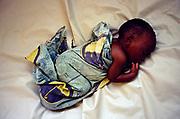 A new born baby asleep in a cot in the hospital in Ruyigi, Burundi