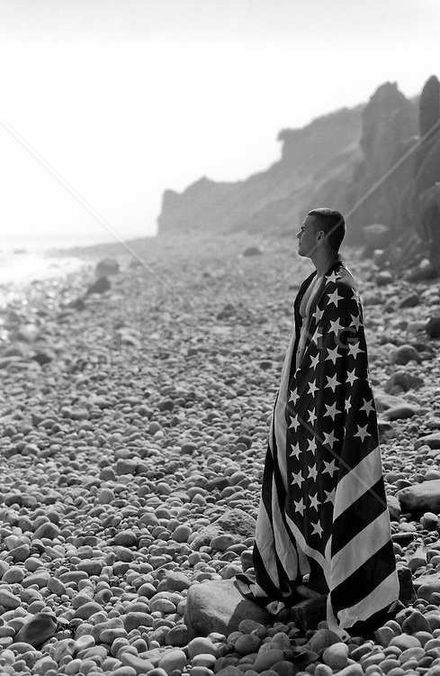 man draped in an American Flag standing on a rocky beach in Montauk, NY
