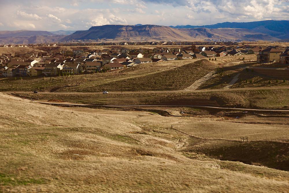 Amtrak Zephyr landscape view with grassland and village west of Denver on Train line.