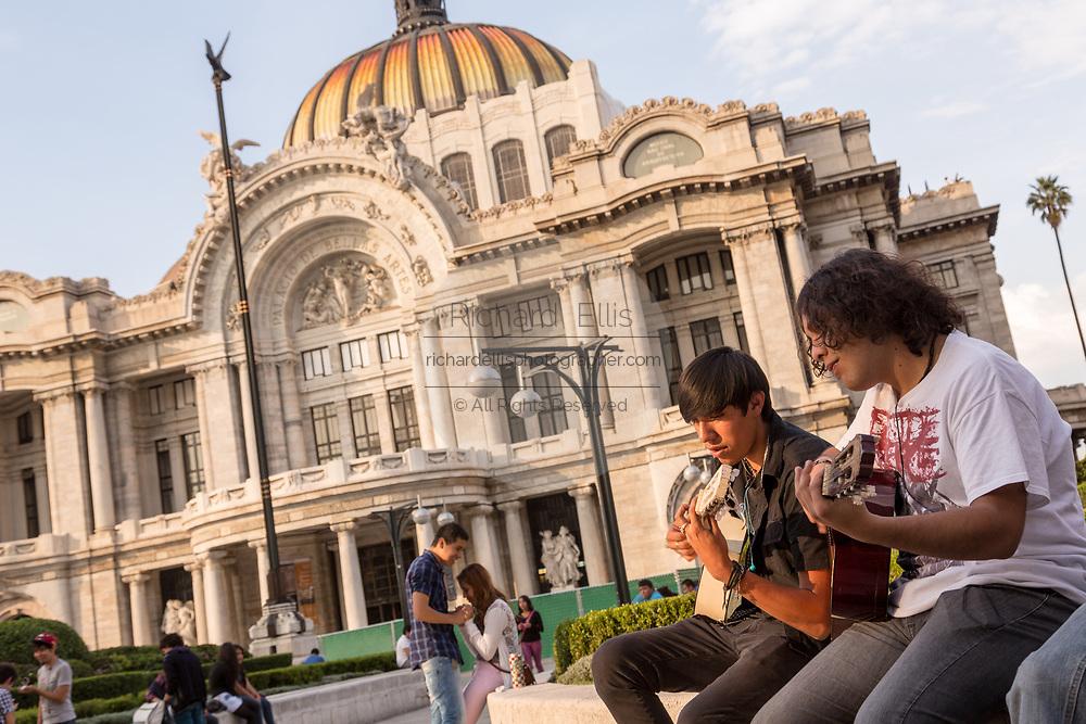 Mexican teens play guitar in Alameda Central park outside the Palacio de Bellas Artes in Mexico City, Mexico.