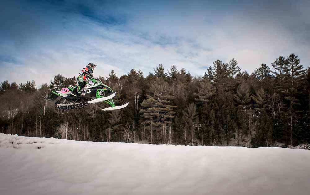 Female Snow Cross snowmobile racer Morganne Sterl practices on a track in Belmont, NH.