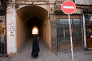 A lone woman in chador ('tent') walks in the old city, Yazd, Iran.