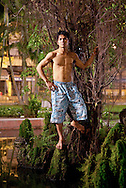 A young bia hoi (restaurant serving cheap beer) worker poses shirtless standing on a rock feature in a public park. Hanoi, Vietnam, Southeast Asia