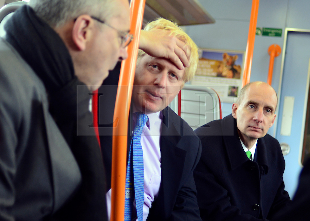 © Licensed to London News Pictures. 14/05/2013. London, UK (Left to right) Transport for London's Commissioner, Sir Peter Hendy CBE, Boris Johnson, Lord Adonis, Chairman of the Crossrail 2 Task Force for London First, talk on a train back to Waterloo Station in Central London. The Mayor of London, Boris Johnson, leads a short walkabout around Wimbledon High Street to meet local people as he helps launch a public consultation on proposed routes for Crossrail 2. Today 14th May 2013. Photo credit : Stephen Simpson/LNP