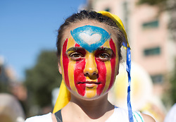 """A young Catalan separatist wears a """"estelada"""" flag makeup as she joins tens of thousands in the centre of Barcelona during 'La Diada', the annual festival to mark National Day of Catalonia, to demand the independence of Catalonia."""