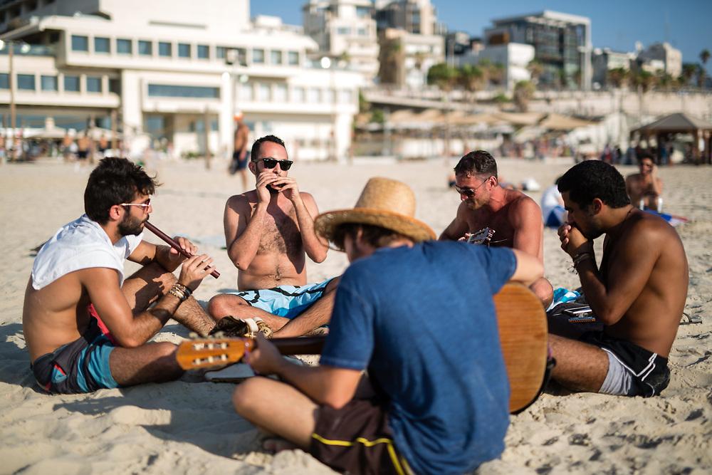 Israelis play musical instruments and sing at Frishman Beach, in Tel Aviv, Israel, on July 21, 2015.