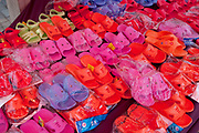Brightly coloured plastic shoes for sale at a market in De Hui city, Jilin Province. North Eastern China.