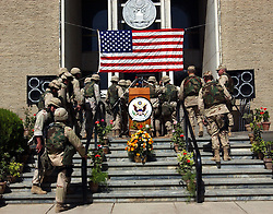 KABUL,AFGHANISTAN - SEPT. 11:  American Marines walk back into the American Embassy after they listened to a speech in Kabul, Afghanistan September 11,2002 where remains of the World Trade Center were laid as a symbolic gesture for those that died in the attack one year ago.While Americans are remembering the attack, most Afghans are trying to forget the decades old war which killed more than a million people here in Afghanistan. (Photo by Ami Vitale/Getty Images)