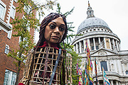 Little Amal, a giant puppet of a Syrian refugee girl fleeing conflict, walks from St Pauls Cathedral to the Globe Theatre on 23rd October 2021 in London, United Kingdom. The 3.5-metre puppet, which is nearing the end of an 8,000km journey from the Turkish-Syrian border to Manchester in support of refugees, climbed the steps of St Pauls Cathedral to present a wood carving of a ship at sea from St Pauls birthplace at Tarsus in Turkey to the dean.