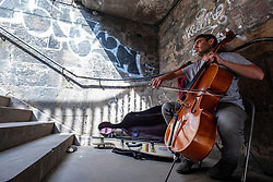Edinburgh, Scotland, UK. 14 May 2019. A busker playing cello for passing tourists sits inside an old stairway in the heart of the Old Town of Edinburgh, Scotland.