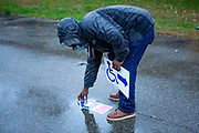 Brooklyn, NY - 1 November 2020. Voters in Brooklyn's Midwood neighborhood stood in line in a light rain at a polling place in Brooklyn College to cast their ballots on the last day of early voting in the 2020 presidential election in New York. After the last of the voters were in the quadrangle a poll worker took up directional signs.