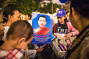 """30 JANUARY 2013 - PHNOM PENH, CAMBODIA:   People buy portraits of the late Cambodian King Norodom Sihanouk in Phnom Penh. Sihanouk (31 October 1922- 15 October 2012) was the King of Cambodia from 1941 to 1955 and again from 1993 to 2004. He was the effective ruler of Cambodia from 1953 to 1970. After his second abdication in 2004, he was given the honorific of """"The King-Father of Cambodia."""" Sihanouk held so many positions since 1941 that the Guinness Book of World Records identifies him as the politician who has served the world's greatest variety of political offices. These included two terms as king, two as sovereign prince, one as president, two as prime minister, as well as numerous positions as leader of various governments-in-exile. He served as puppet head of state for the Khmer Rouge government in 1975-1976. Most of these positions were only honorific, including the last position as constitutional king of Cambodia. Sihanouk's actual period of effective rule over Cambodia was from 9 November 1953, when Cambodia gained its independence from France, until 18 March 1970, when General Lon Nol and the National Assembly deposed him. Upon his final abdication, the Cambodian throne council appointed Norodom Sihamoni, one of Sihanouk's sons, as the new king. Sihanouk died in Beijing, China, where he was receiving medical care, on Oct. 15, 2012. His cremation is scheduled to take place on Feb. 4, 2013. Over a million people are expected to attend the service.        PHOTO BY JACK KURTZ"""