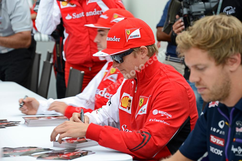 Sebastian Vettel (Red Bull-Renault) Kimi Raikkonen and Fernando Alonso (both Ferrari) signing autographs during 2014 British Grand Prix at the Silverstone. Photo: Grand Prix Photo