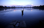 A young boy leaps into a baray (reservoir bordering the temples) to cool off, Angkor Was