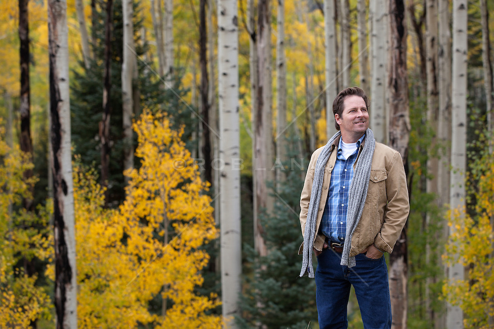 man enjoying a stroll in the woods during the changing of the leaves in Autumn