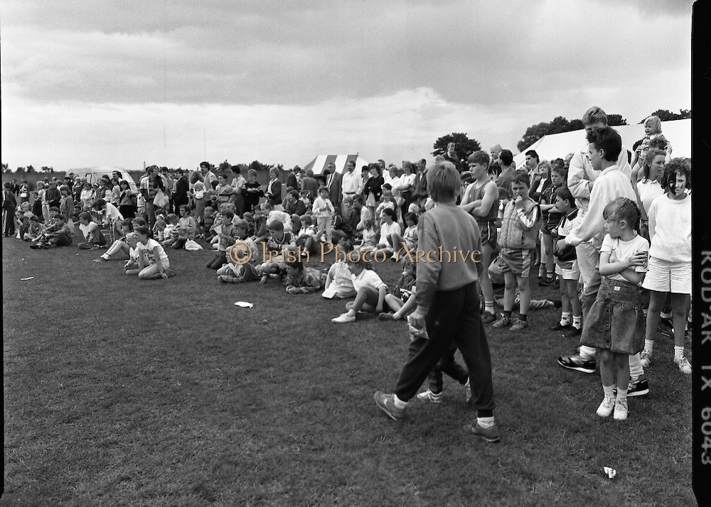 """Guinness Family Day At The Iveagh Gardens. (R83)..1988..02.07.1988..07.02.1988..2nd  July 1988..The family fun day for Guinness employees and their families took place at the Iveagh Gardens today. Top at the bill at the event were """"The Dubliners"""" who treated the crowd to a performance of all their hits. Ireland's penalty hero from Euro 88, Packie Bonner, was on hand to sign autographs for the fans...Image shows the children intently watching the Garda dogs doing their display."""