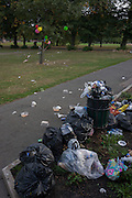 Overflowing bin and birthday party balloons left tied in a tree of Ruskin Park, south London borough of Lambeth, UK.