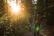 Climbers Chris Moorehead (r-l) and Brian Polagye hike out through forest as the sun sets in the Monte Cristo area, Mount Baker-Snoqualmie National Forest, Washington.