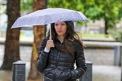 © Licensed to London News Pictures. 10/06/2019. London, UK. A woman shelters from the rain beneath an umbrella  as rain falls in the capital. The Met Office has just issued an amber warning for more rain, covering London and parts of southeast England later today Photo credit: Dinendra Haria/LNP