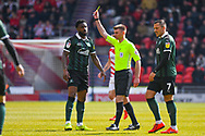 Yann Songo'o of Plymouth Argyle (4) is booked and receives a caution and a yellow card from Ollie Yates (Referee) during the EFL Sky Bet League 1 match between Doncaster Rovers and Plymouth Argyle at the Keepmoat Stadium, Doncaster, England on 13 April 2019.