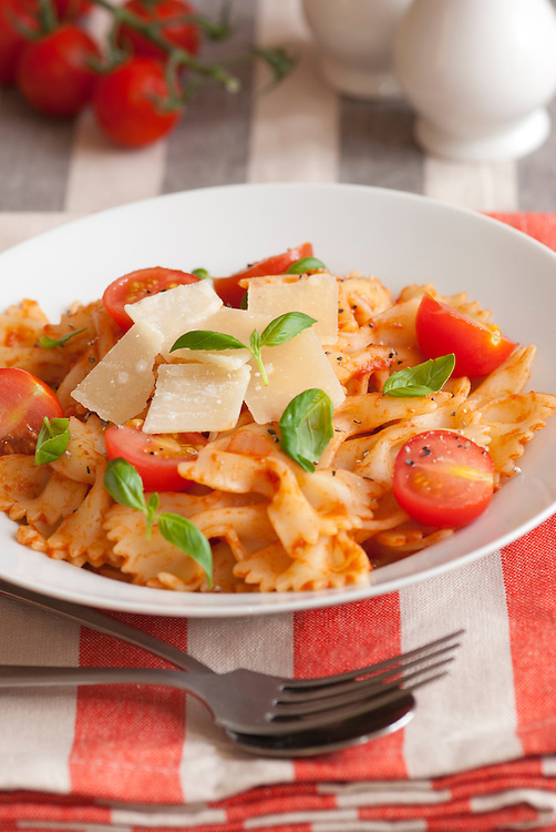 Farfalle in tomato sauce with basil and grated Parmesan