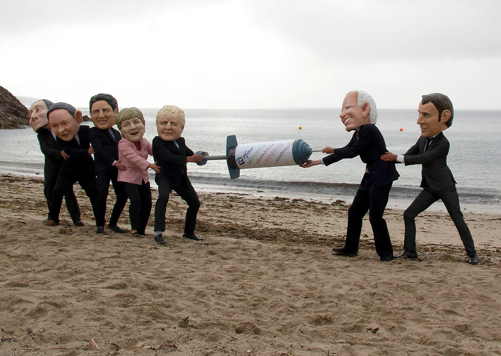 People dressed as members of the G7 play tug of war with a big vaccine needle, on Swanpool beach, Cornwall. This is part of the People's Vaccine group, protesting at the G7. 11th June 2021. Anna Hatfield/Pathos