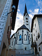 """San Luzi protestant parish church was built in Gothic style in Zuoz, one of the best preserved villages in Upper Engadine. Visit Graubünden canton in Switzerland, the Alps, Europe. Sgraffito (or scraffito, plural: sgraffiti) is a technique of wall decor where layers of plaster tinted in contrasting colors are applied to a moistened surface. The Swiss valley of Engadine translates as the """"garden of the En (or Inn) River"""" (Engadin in German, Engiadina in Romansh, Engadina in Italian). The church steeple pierces a blue sky."""
