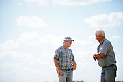 Farmers talking on a farm in Iowa.<br />