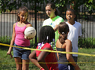 Middletown, New York - A counselor teaches a girl how to serve a volleyball during a game at the Middletown YMCA summer camp on August 20, 2010.