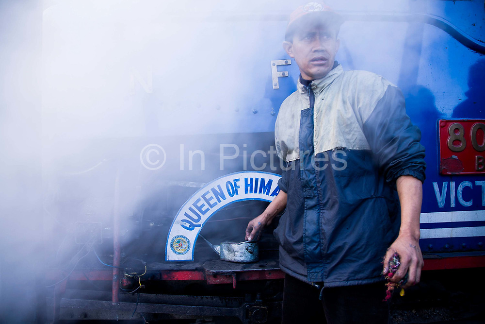 """Train workers prepare a steam train for the daily run from Darjeeling to Kurseong as well as to Siliguri. The Darjeeling Himalayan Railway, nicknamed the """"Toy Train"""", is a narrow-gauge railway from Siliguri to Darjeeling in West Bengal, run by the Indian Railways. It was built between 1879 and 1881 and is about 86 km long. The elevation level is from about 100 m at Siliguri to about 2200 m at Darjeeling. It is still powered by a steam engine and travels daily between the two towns.  It is now classed as a World Heritage Site by UNESCO. India."""