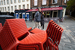 Edinburgh, Scotland, UK. 17 October 2020. Saturday afternoon in Edinburgh city centre during 16 day short circuit lockdown and bars are closed but cafes remain open. Streets in the Old town are very quiet and reminiscent of the eerie emptiness seen during the full lockdown earlier this year. Chairs stacked outside closed restaurant in Grassmarket.  Iain Masterton/Alamy Live News