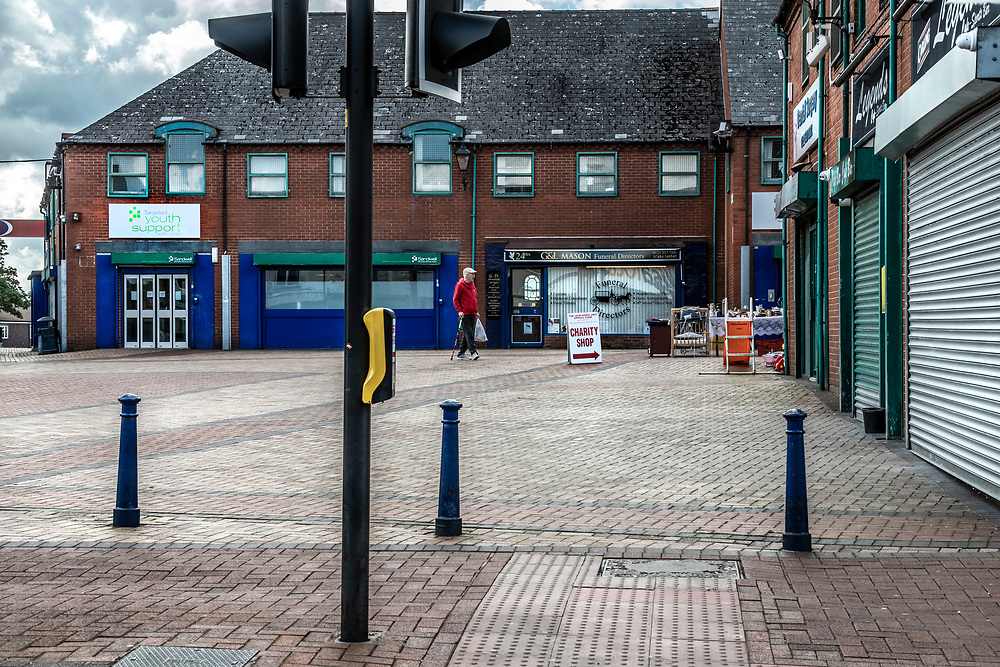 Elderly man walking towards a charity shop in the pedestrian precinct are of Tipton, northwest of Birmingham, West Midlands. The area is surrounded with closed down shops.