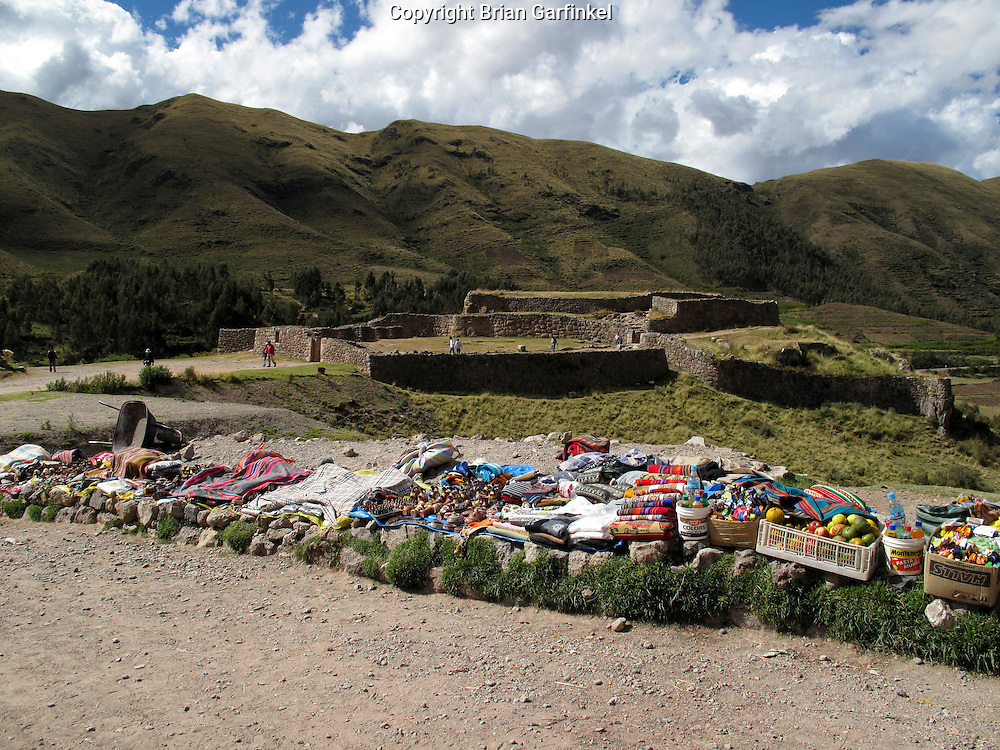 Local Peruvians sell fruit and other goods on the side of a road near the Puca Pucara Inca ruins outside of Cusco Peru